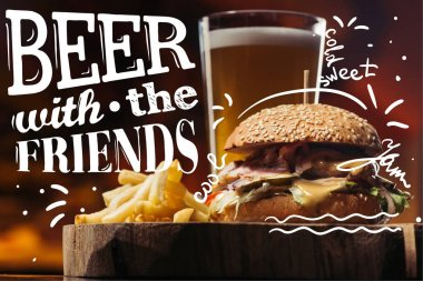 tasty burger with turkey, french fries and glass of beer with