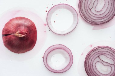 top view of red onion with slices and rings on white surface with pink watercolor blots
