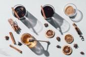 Fotografie Draufsicht auf Gläser mit Glühwein, Honig und braunem Zucker auf weißer Tischplatte
