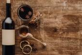Fotografie erhöhter Blick auf Glühwein, Honig und Weinflasche auf Holztisch