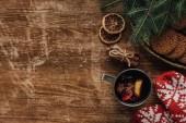 erhöhter Blick auf Glühwein im Becher, Fäustlinge und Plätzchen auf hölzerner Tischplatte, Weihnachtskonzept
