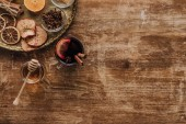 Fotografie Draufsicht auf Tasse Glühwein und Honig auf Holztisch