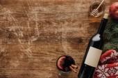 Fotografie Draufsicht auf Weinflasche, Tasse Glühwein und Honig auf Holztischplatte, Weihnachtskonzept
