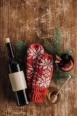 Fotografie Draufsicht auf Weinflasche, Glühweinbecher und Winterhandschuhe auf Holztischplatte, Weihnachtskonzept