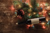 Fotografie Draufsicht auf Weinflasche, Glühweinbecher und Girlanden auf Holztischplatte, Weihnachtskonzept