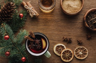 top view of spice mulled wine and fir twigs with baubles on wooden tabletop, christmas concept