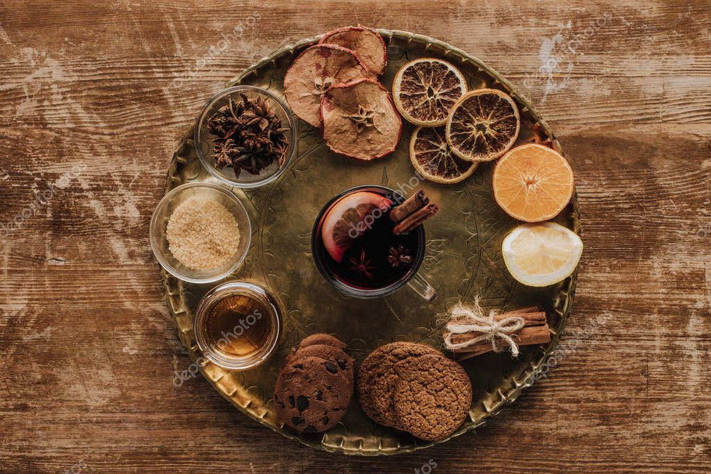 Top view of mulled wine in cup and cookies on round tray on wooden table stock vector