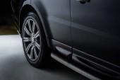 Fotografie zblízka pohled luxusní lesklé černé auto na tmavém pozadí