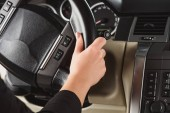 cropped shot of woman with hand on steering wheel driving car