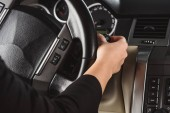 Oříznuté záběr ženy zapnutí stěračů při jízdě auto sám