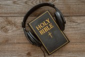 Fotografie top view of holy bible with headphones on wooden tabletop