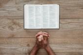 vágott szemcsésedik-ból afrikai amerikai férfi imádkozik a Szent Biblia, a rusztikus, fából készült asztal