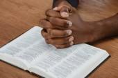 Oříznout záběr afroamerické muže modlit s holy bible na dřevěný stůl