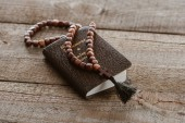 Fotografie close-up shot of new testament book with beads on wooden table