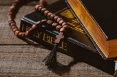 Photo close-up shot of holy bibles with beads on wooden table