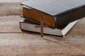 close-up shot of stacked holy bibles with cross on wooden table