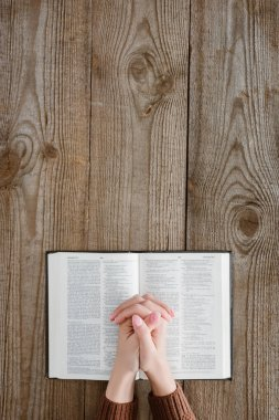 cropped shot of woman praying with holy bible on wooden table