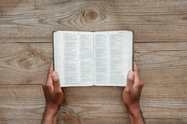 cropped shot of man holding holy bible over wooden table