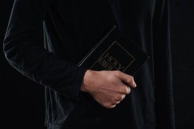 Cropped shot of priest holding holy bible isolated on black stock vector