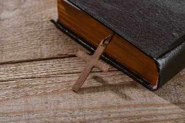 close-up shot of holy bible with cross on wooden table
