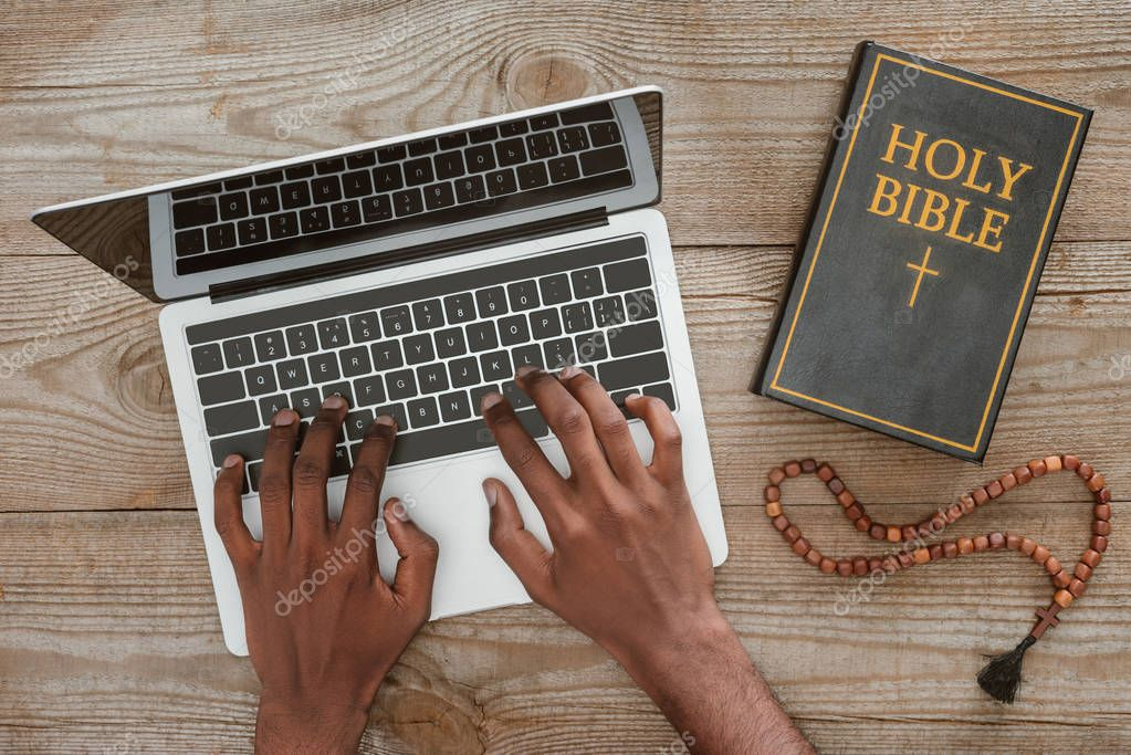 Cropped shot of man working with laptop with holy bible and beads on wooden tabletop stock vector