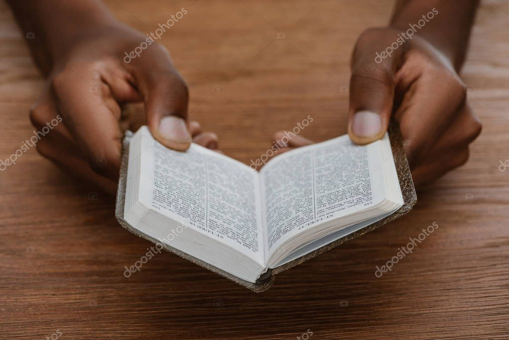 Cropped shot of african american man reading holy bible on wooden table stock vector