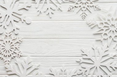 flat lay with decorative snowflakes on white wooden tabletop with blank space in middle