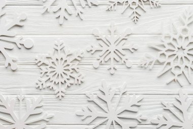 flat lay with decorative snowflakes on white wooden tabletop