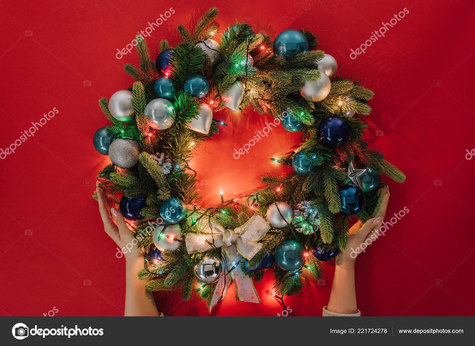gedeeltelijke weergave van vrouw met handgemaakte kerst krans met verlichting stockfoto