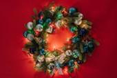 Draufsicht der Adventskranz dekoriert mit Spielzeug und Lichter auf rotem Grund