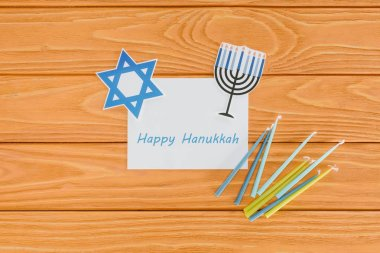 Flat lay with happy hannukah card, candles and paper holiday signs on wooden tabletop, hannukah concept stock vector