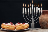 close up view of traditional sweet doughnuts, clay jug and menorah with candles isolated on black, hannukah holiday concept