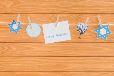 top view of happy hannukah card and holiday paper signs pegged on rope on wooden tabletop, hannukah concept