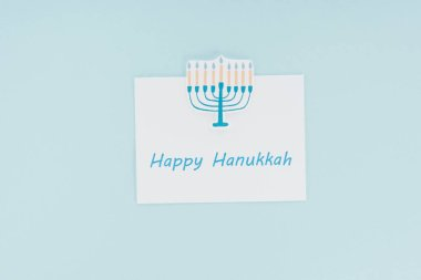 Top view of happy hannukah card and paper menorah sign isolated on blue, hannukah concept stock vector
