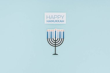 Top view of happy hannukah card and paper menirah sign isolated on blue, hannukah concept stock vector