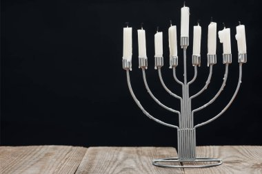 Close up view of jewish menorah with candles for hannukah holiday celebration on wooden tabletop isolated on black, hannukah concept stock vector