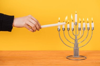 Partial view of woman lighting candles on menorah isolated on yellow, hannukah holiday concept stock vector