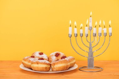 Close up view of sweet doughnuts and menorah with candles on wooden surface isolated on yellow, hannukah concept stock vector