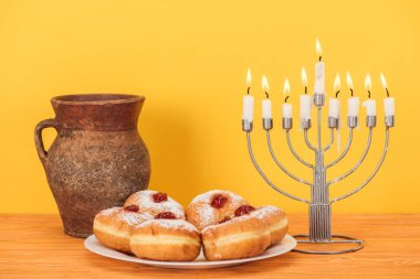Close up view of sweet doughnuts, clay jug and menorah on wooden surface on yellow backdrop, hannukah concept stock vector
