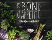 Draufsicht auf verschiedene frische Gemüsesorten auf Holztischplatte mit Kopierraum, leckerer Appetit-Schriftzug