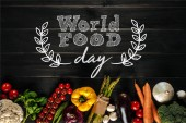 different fresh vegetables lying in row on wooden tabletop with world food day inscription