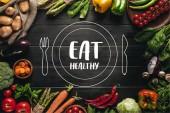 Fotografie rám z organických čerstvé zeleniny na vyhození na dřevěnou desku s jíst zdravé nápis s nakreslené talíř a příbory