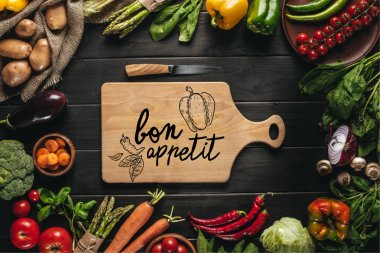 Top view of cutting board with knife and organic fresh vegetables around on wooden tabletop, bon appetit lettering stock vector