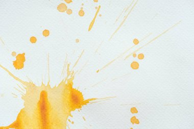 Artistic orange watercolor splatters and blots on white paper stock vector