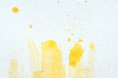Yellow watercolor strokes and splatters on white paper background stock vector