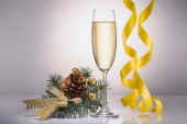 close up view of glass of champagne, christmas decoration and confetti on grey backdrop
