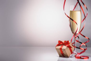 close up view of glass of champagne and wrapped gift on grey backdrop