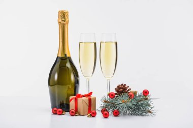 Close up view of bottle and glasses of champagne, christmas decorations and present on white background stock vector