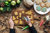 partial view of woman decorating homemade christmas cookies with food grade ink on wooden surface