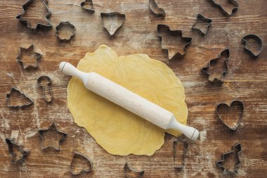 flat lay with raw dough, rolling pin and cookie cutters arranged on wooden tabletop
